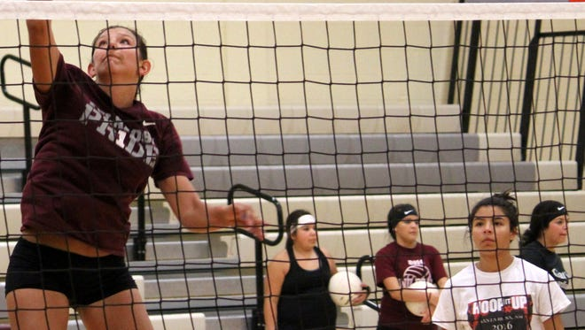 Alex Veyna, left, spikes a ball during practice Tuesday evening at the Michael Dorame Gymnasium.