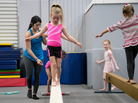 Gwen Todd, 4, left, practices walking on the balance beam during her class on Monday at Gymnastic World in south Fort Myers.