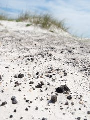 Asphalt still awaits removal along the sands of Gulf