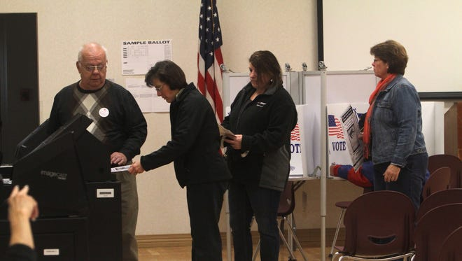 Election Inspector Jack Hilburger watches as Barb Egan casts her ballot in Irondequoit on Tuesday.