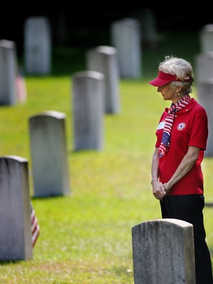 Sharon Courey paused to reflect at the grave markers of local veterans during Memorial Day. Taps was played, speeches were made and old friends reunited at the Oakland Cemetery for the annual Memorial Day celebration to honor those who have given their lives in American's wars.