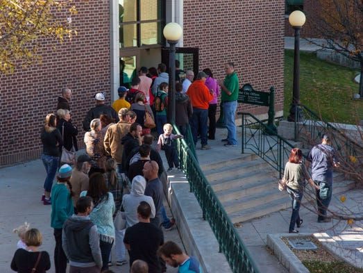 Cedar City residents wait to vote in a line outside