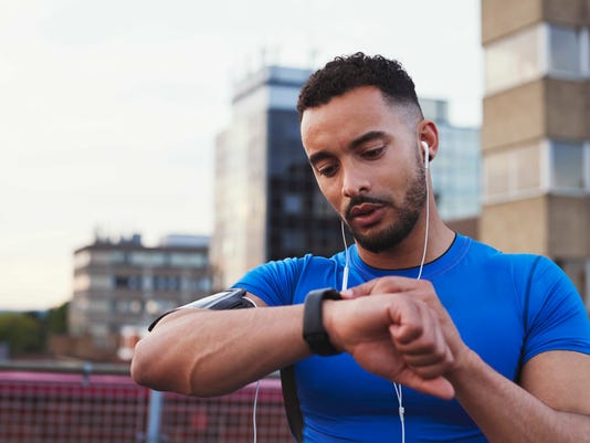 Male runner uses app on smartwatch in urban street, close up