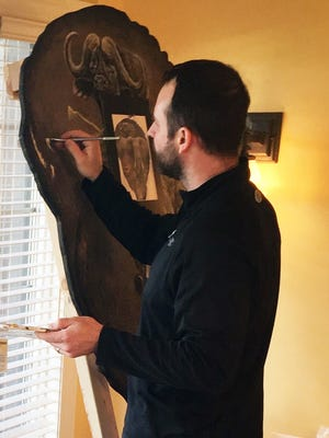 Eric Peterson works on a painting on an elephant ear for a customer.