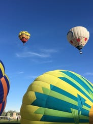Hot air balloons inflate and take off from the Chamblee
