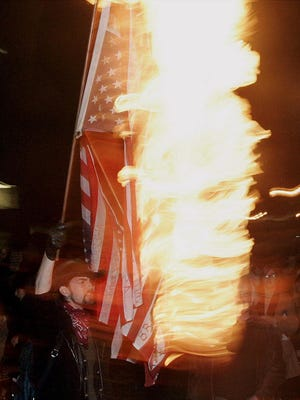 A protester burns an American flag to protest President Bush's second inauguration during a march in downtown Portland, Ore., in this Jan. 20, 2005, file photo.