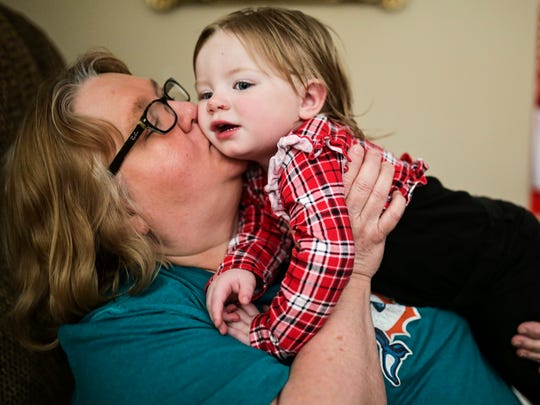 Teresa Grider of Elizabethtown, left, kisses her youngest grandchild Laney, 1, Thursday afternoon after she woke up from a nap.The child was born addicted to drugs and is dealing with a myriad of health issues. Grider quit her job as she is currently raising five of her grandchildren as the mother struggles with drug addiction. Grider's son, the father, lives nearby and visits them regularly.   In the past, family members like Grider could receive up to $300 per month per child to cover expenses of taking in a child through the Kinship Care program. However, the state ended the program in 2013 for budget reasons.  April 27, 2017