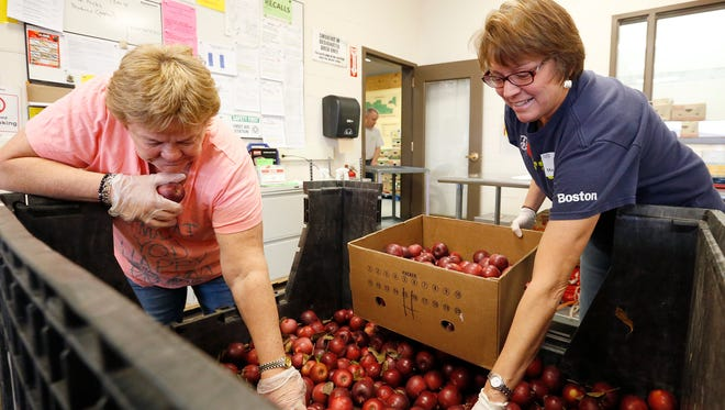 Diana Schuler and Maggie Sullivan sort through a bin full of apples to place into 35-pound boxes Saturday at the Food Bank of the Southern Tier during Make a Difference Day. The apples will be distributed to the food bank's mobile food truck and food pantries across the six counties the organization serves.
