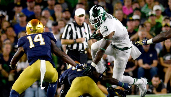 Michigan State University sophomore running back LJ Scott (3) leaps over a defender on a rush in the first half of the Spartans game against Notre Dame Saturday, Sept. 17, 2016 in South Bend, Ind.