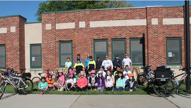 Gary Lubisco, Sue Gavin, Dunellen Police Department Members, Dunellen Fire Department Members, Anthony DeFlippis and students from Faber school by the Pallet Bike Racks that were donated.