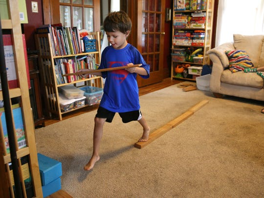 Schuyler Peck, 5, does some balance exercises to help him strengthen his core muscles.  He has been diagnosed with core muscle weakness and his mother, Sharon Peck fears he will fall behind in school.