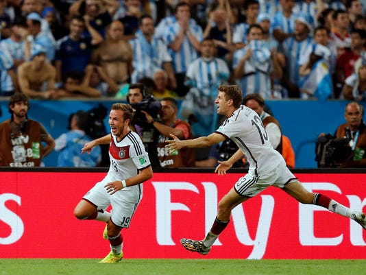 Germany's Mario Goetze, left, celebrates with Thomas Mueller after scoring the opening goal during the World Cup final soccer match between Germany and Argentina at the Maracana Stadium in Rio de Janeiro, Brazil, Sunday, July 13, 2014. Germany beat Argentina 1-0 to win its fourth World Cup title. (AP Photo/Frank Augstein)