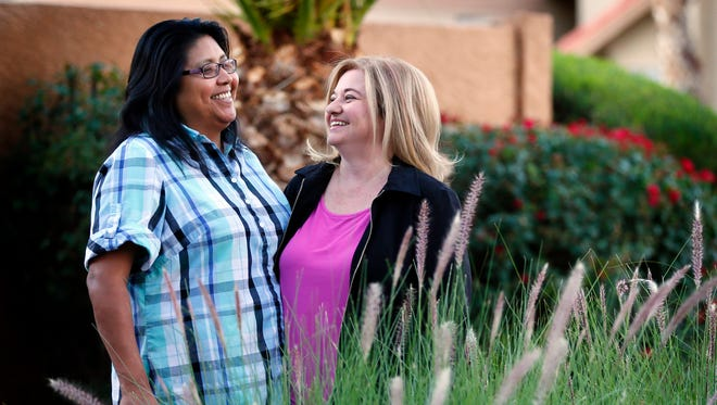 In this Nov. 9, 2015, photo, Cleo Pablo and her wife, Tara Roy-Pablo, stand outside their home in Phoenix. Pablo married her longtime partner when gay weddings became legal in Arizona, but the Ak-Chin Indian Community doesn''t recognize same-sex marriages and has a law that prohibits unmarried couples from living together.