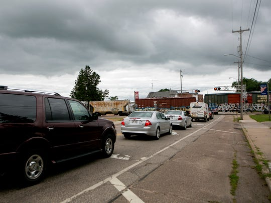 Cars stopped on Main Street wait for a train to cross
