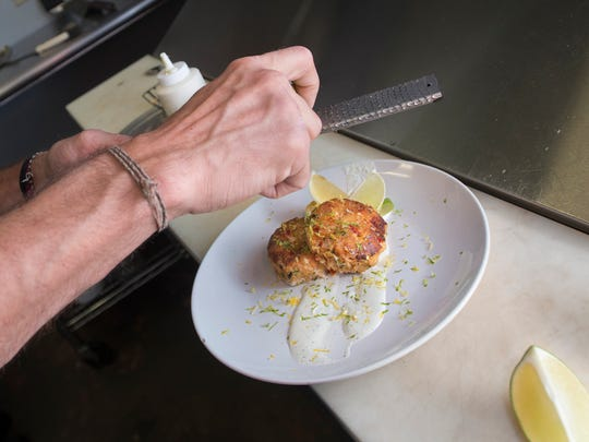 Chef Nathan Butner garnishes his gluten-free crab cakes with tequila lime crème fraîche dish at South Market restaurant in Pace on Monday, August, 28, 2017.  South Market is one of the local restaurants competing in the Florida Chef Challenge, a fundraiser for Feeding the Gulf Coast.