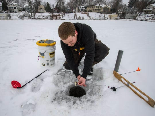 Mitch Erickson of Okauchee resets his line during the 4th Annual Ice Fisheree & Raffle hosted by Bucky's Lakeside Pub and Grill in Okauchee in 2016.