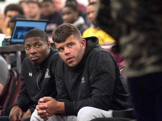 """SIUC senior wide receiver Darrell James, of Fort Worth, Texas, and senior quarterback Sam Straub, of Ames, Iowa, listen intently as sports radio personality Rachel Baribeau, of Nashville, gives a presentation to the SIUC football team Monday, March 19, 2018, at the SIU Arena in Carbondale, Ill. """"[Baribeau's] talk was different than any talk I've been a part of in the four years I've been [at SIUC],"""" Straub said. """"A lot of people will come in and talk about things that maybe they haven't been through and it doesn't sound as authentic. ... [Baribeau] has those personal experiences."""""""