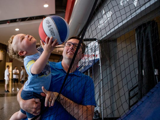 Alberta resident Shaun Hall holds his 2-year-old son, Luca Hall, as Luca attempts to make a basket at NBA Summer League on Sunday.