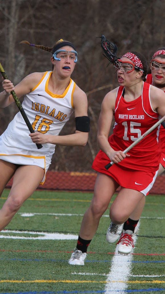 Mahopac's Kim Harker (18) pushes the ball up past North Rockland's Aleya Corretjer (15) during girls lacrosse at Mahopac High School on April 2, 2015. North Rockland defeated Mahopac 8-7.