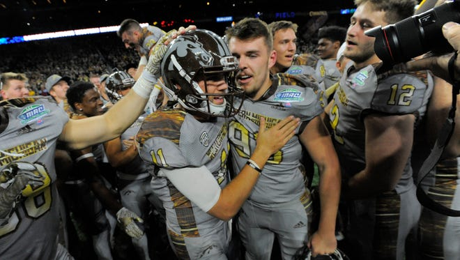 Western Michigan quarterback Zach Terrell (11) celebrates with Austin Regan (93) after beating Ohio University for the MAC championship Friday night at Ford Field.