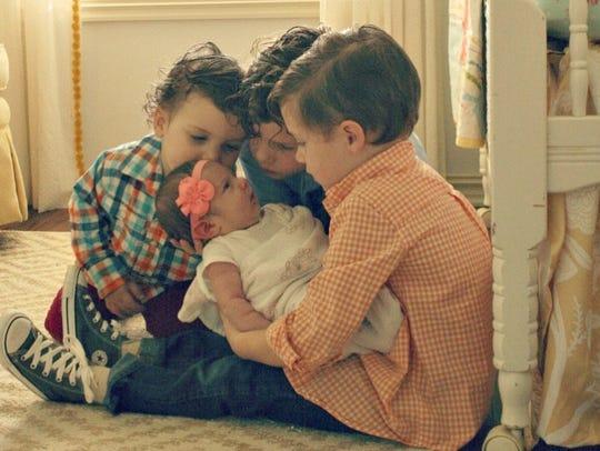 Joshua, Jacob and Ethan Walker admiring their new sister,