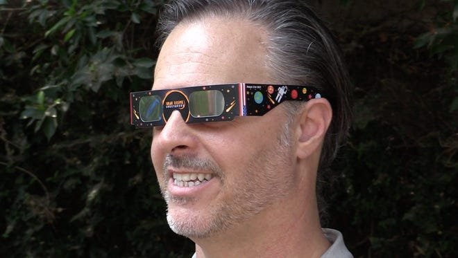 Astro-photographer Brian Valente sports filtered glasses for the summer eclipse