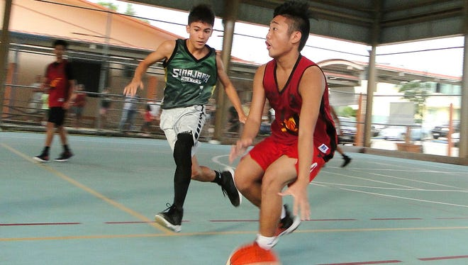 Team Unity's Sean Cuenco brings the ball down the court as the Sinajana Rockers' Chuckie White defends in an Under-16 game in the Sinajana Youth Basketball League.