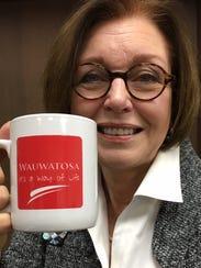 Wauwatosa Mayor Kathy Ehley hoists a mug displaying