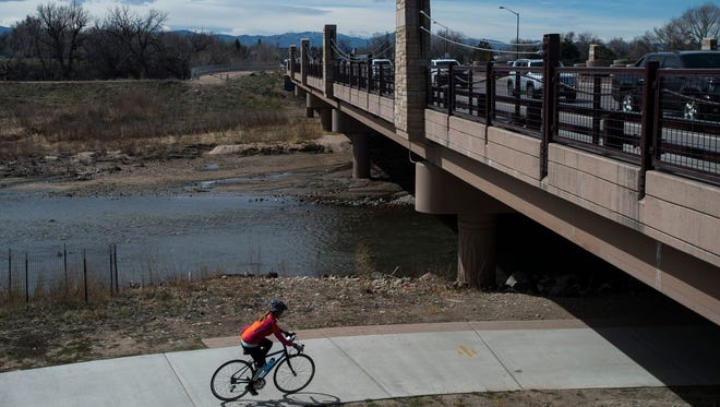 A cyclist rides under the East Mulberry bridge spanning over the Cache La Poudre River on Friday, March 30, 2018, in Fort Collins, Colo.