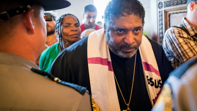 Reverend William J. Barber argues with State Troopers at the doors of the state capitol building during a protest organized by Kentucky Poor People's Campaign in Frankfort, Ky., Monday, June 4, 2018. Anti-poverty activists were denied group access to Kentucky's Capitol following an outdoor rally that included a denunciation of the nation's first work requirements for Medicaid. (AP Photo/Bryan Woolston)