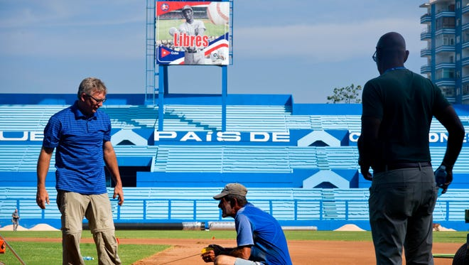 Murray Cook, left, and Phil Bradley, right, from the Major League Baseball Players Association talk to a worker during the refurbishing of the Latinoamericano stadium where the Cuban national baseball team and the Tampa Bay Rays will play in Havana on Tuesday.