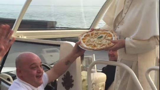 An employee of PIzzeria Don Ernesto in Naples, Italy, hands Pope Francis a pizza on Sunday.