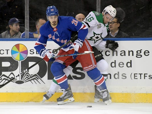 New York Rangers left wing Chris Kreider (20) battle for control of the puck with Dallas Stars' Jason Dickinson during the first period of an NHL hockey game Monday, Dec. 11, 2017, at Madison Square Garden in New York. (AP Photo/Bill Kostroun)