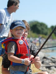 Cooper Schmitz, 4, fishes with his mother, Audrey, during the Otter Street Fishing Club's Kid's Fisheree in August 2012 at Menominee Park in Oshkosh. This year's event is Aug. 12.