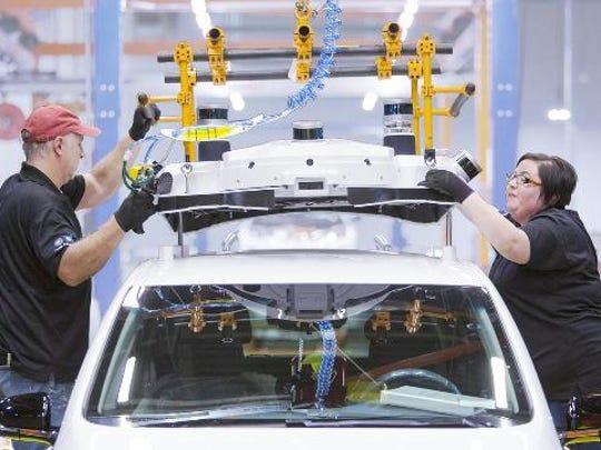 Line workers at General Motors Co.'s Lake Orion plant assemble an autonomous Bolt EV.