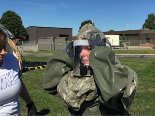Tech Sgt. Sabrina Roberts at right puts on her chemical protective suit during a training exercise at the 179th Airlift Wing of the Ohio Air National Guard base Thursday.