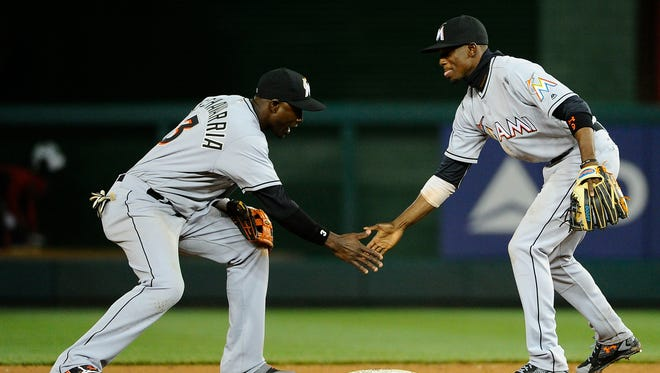 Marlins shortstop Adeiny Hechavarria, left, and second baseman Dee Gordon celebrate after defeating the Nationals.