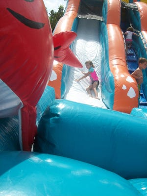 Children have fun on a water slide during the kickoff to Lumberton Library's Summer Reading Program.