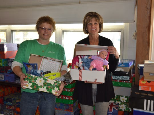 Joyce Tucker, left, and Judy Journay display some of the many boxes that were filled for Operation Christmas Child at First United Methodist Church in Bellevue.