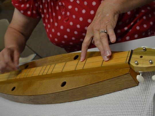 Laptop dulcimers can be expensive and made of exotic woods, or they can be inexpensive like the ones students learn on in Pat Rife's class, which are made of plywood wall paneling. Either way, students can easily learn to play beautiful music on them.