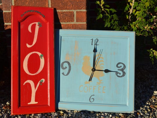 These old kitchen cupboard doors were repurposed into, on left, a holiday sign and, on right, a working clock. The clock was redone using distressing techniques, which gives an antique, familiar feel to the piece. The signs are available for purpose from Twice Loved, an online business based in Fremont.