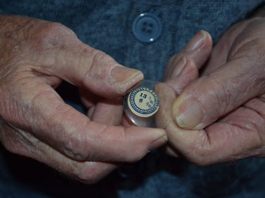 Richard Sneary holds one of the dozens of watch crystals