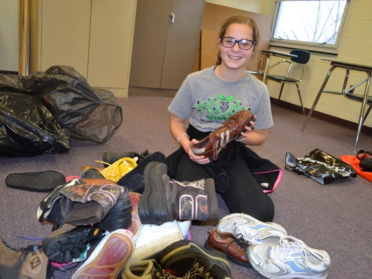 Hannah Schulte sorts and bags shoes for storage at