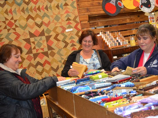 From left, sisters Chris Schue, Donna Scates and Lyn Fowl traveled from out of town to spend the day shopping at The Door Mouse on Monday. The sisters said the shop's friendly service and dozens of quilt displays set it apart from other quilt stores.