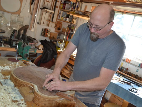 Denny Kopp carves into the walnut back of a guitar that will be shipped to a buyer in Spokane.