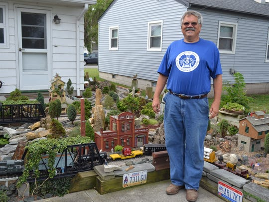 Steve Tusen stands next to the railroad garden he has been creating in his Port Clinton backyard since 1997. The garden is filled with over 100 live miniature and dwarf trees.