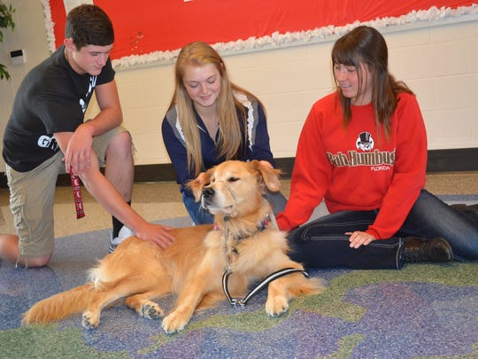 Lansbury, a therapy dog at Lakota Local Schools, gets his ears rubbed by Amber Eubank, center, and receives some extra love from Tyler Wehrle, left, and Sarah Sievers.