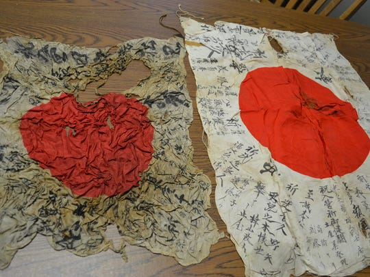 The more deteriorated flag on the left is owned by the Ottawa County Museum, and the flag on the right was obtained by Jeff Brown at an auction. Both flags may one day be returned to the families of the Japanese soldiers that once carried them into battle.