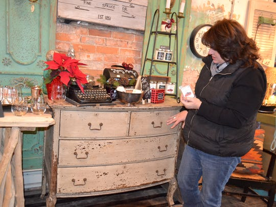 Laurie Shaw with a dresser in her shop, Blue Door.