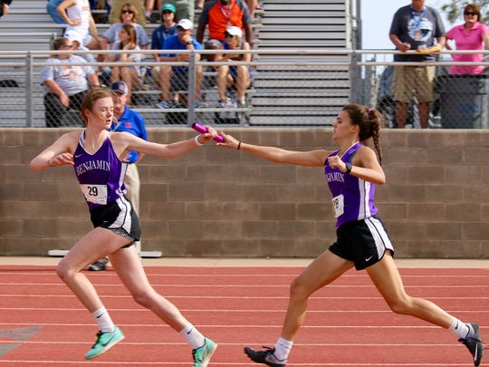 Benjamin's Myca Flowers (left) takes the baton from sister Macy Flowers in the 4x400 relay last week at regionals.
